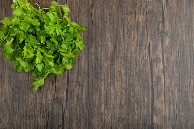 Healthy green parsley leaves placed on wooden surface