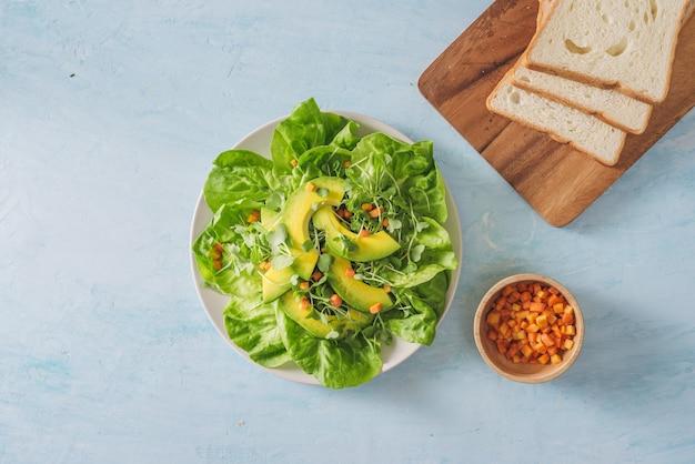 アボカド、キュウリ、ブドウ、パセリ、レタスのヘルシーなグリーンサラダにオリーブオイルドレッシング、バルサミコ酢、粒マスタードを添えて。