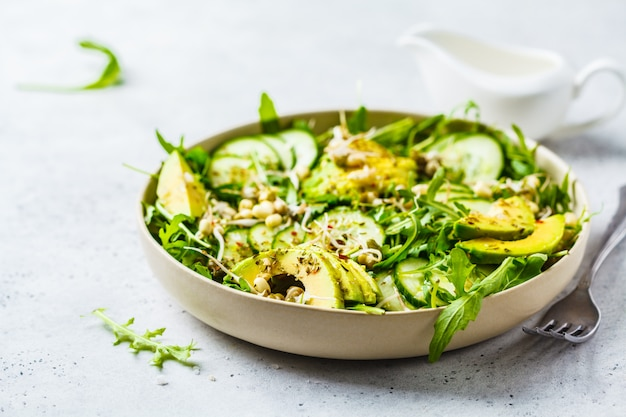 Healthy green salad with avocado, cucumber and arugula in white dish.