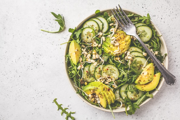 Healthy green salad with avocado, cucumber and arugula in white dish