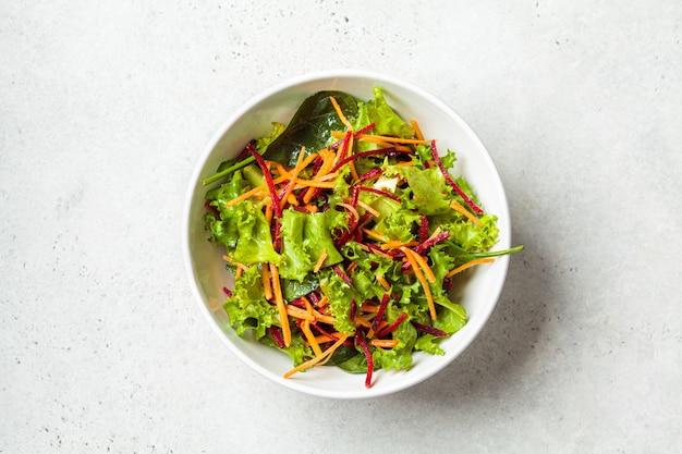 白いボウルにビートとニンジンを入れたヘルシーなグリーンサラダ。ダイエット食品のコンセプト。