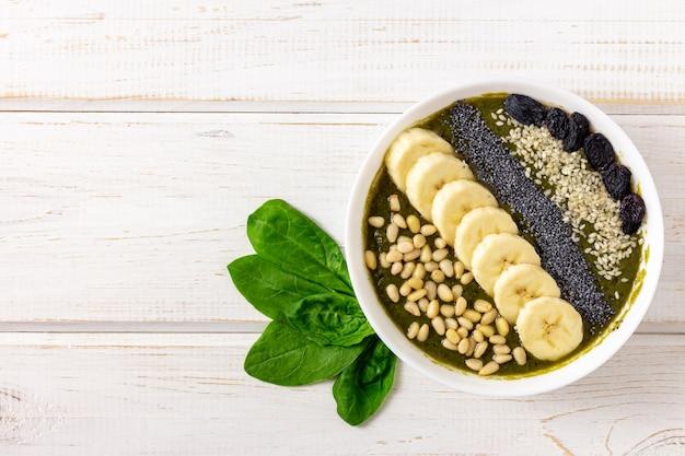 白い木製のテーブルにイラクサ、ほうれん草、バナナと健康的なグリーンスムージーボウル
