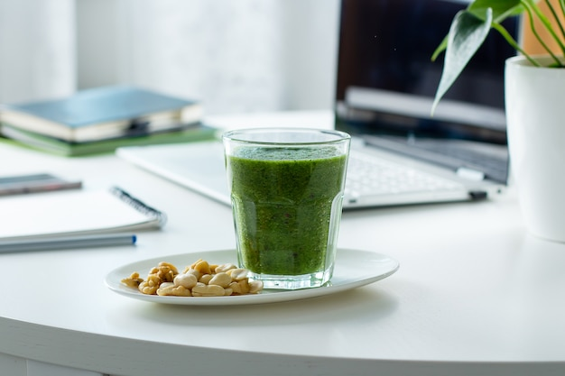 Healthy green smoothie from spinach, kiwi and nuts on workplace working table with laptop