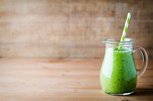 古い木の上のガラスの健康的な緑のスムージー。
