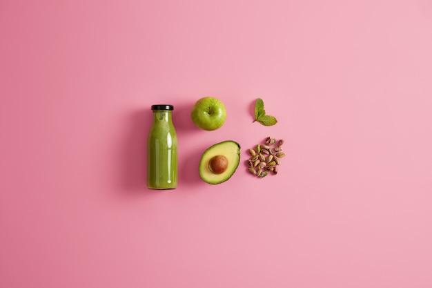 Frullato verde sano a base di mela succosa, avocado, pistacchio e menta. sfondo roseo. bevanda fresca e nutriente per una dieta equilibrata. ingredienti per preparare una bevanda nutriente rinfrescante.