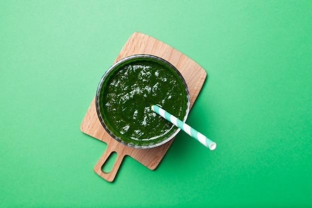 Здоровый зеленый коктейль на зеленом столе. вид сверху