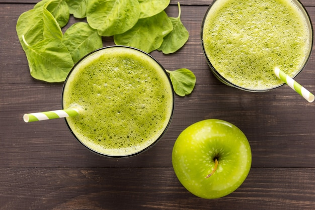 Healthy green smoothie with apple on rustic wood background
