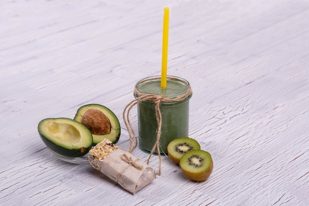 Healthy green smoothie with avocado and kiwi lie on the table