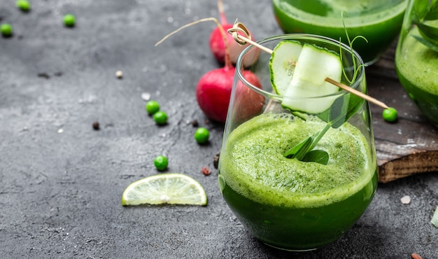 オーガニックグリーン、エンドウ豆、キュウリ、大根、ほうれん草、ライムを使ったヘルシーなグリーンスムージー。健康的なデトックスドリンク。上面図。