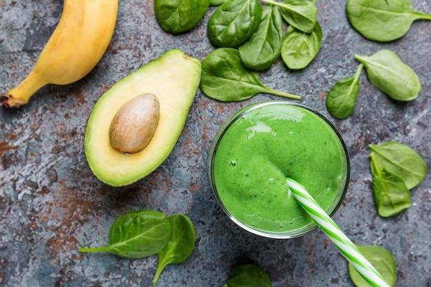 회색 돌 배경의 유리병에 시금치, 아보카도, 바나나, 치아 씨를 넣은 건강한 녹색 스무디, 위쪽 전망.