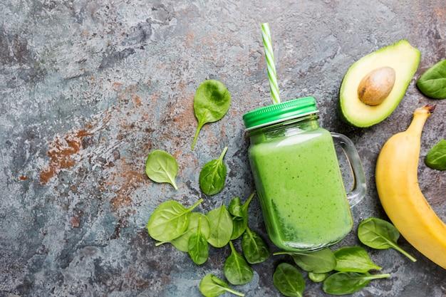회색 돌에 시금치 아보카도 바나나와 치아 씨를 넣은 건강한 녹색 스무디