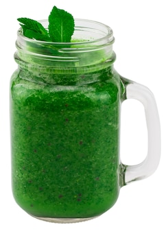 白で隔離の瓶のマグカップにほうれん草と健康的な緑のスムージー。