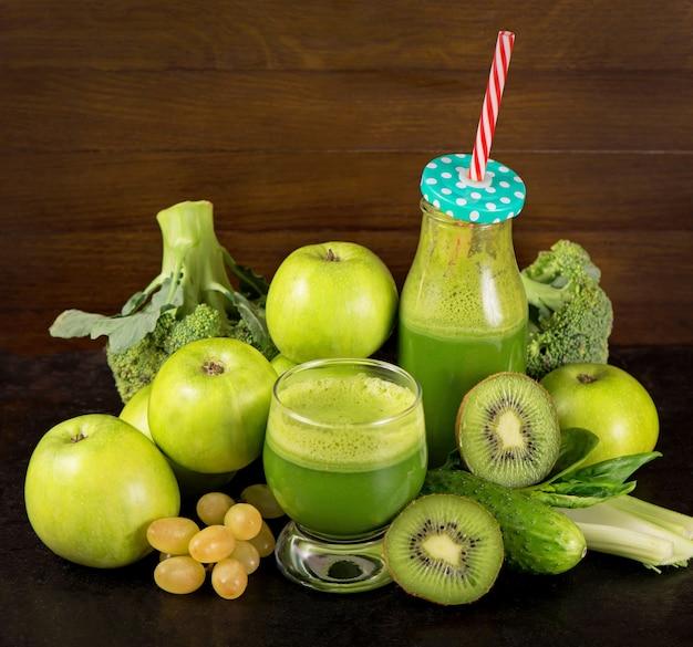 白で隔離の瓶のマグカップにほうれん草と健康的な緑のスムージー
