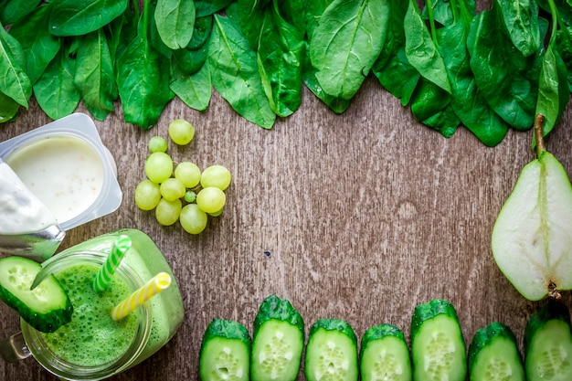 나무 배경에 대해 머그에 시금치를 넣은 건강한 녹색 스무디. 텍스트를 위한 장소가 있는 평평한 위치. 완전 채식 및 건강 식품 개념
