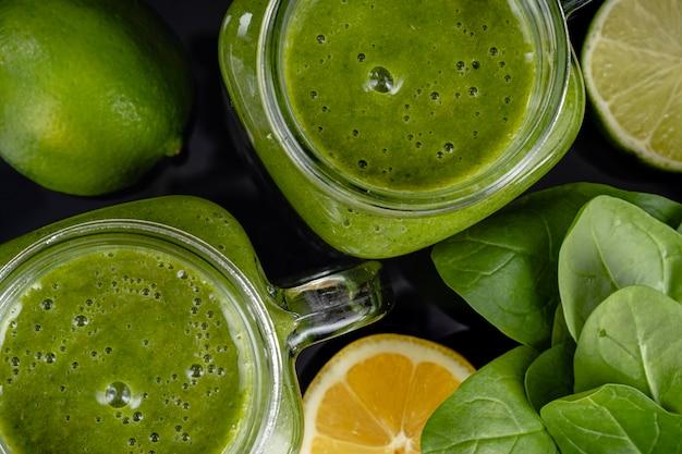 Здоровый зеленый смузи со шпинатом, манго, апельсином, лаймом, яблоком, лимоном в стеклянных банках, вид сверху