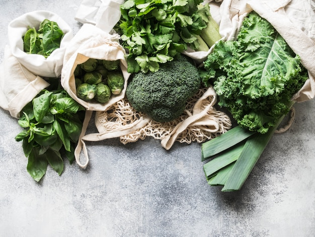 Healthy green vegan ingredients for cooking. various clean green vegetables and herbs in textile bags. products from the market without plastic. zero waste concept flat lay.