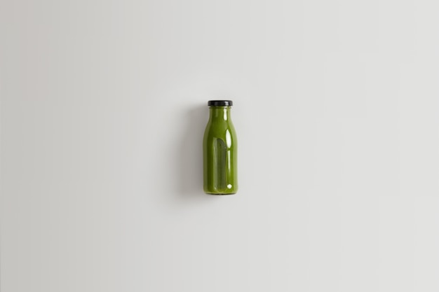 Healthy green vegetable smoothie prepared from spinach, kale and cucmbers blended with water for your proper nutrition. bottle of nutrient beverage of organic ingredients against white background.
