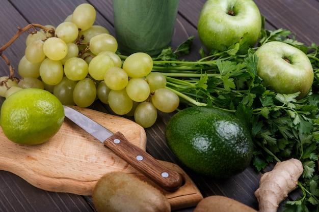 Здоровые зеленые овощи и фрукты для коктейля лежат на столе