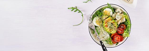 계란, 쌀, 토마토, 아보카도 및 테이블에 블루 치즈와 함께 건강 한 녹색 채식 부처님 그릇 점심.