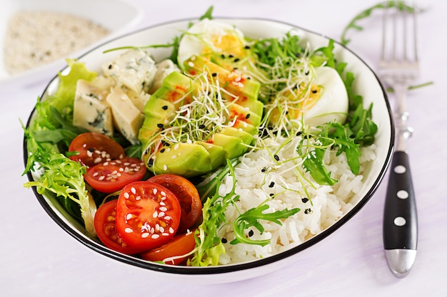 Healthy green vegetarian buddha bowl lunch with eggs, rice, tomato, avocado and blue cheese on table.