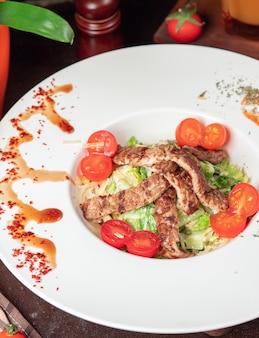 치즈, 체리 토마토, 양상추를 곁들인 건강한 구운 쇠고기 시저 샐러드