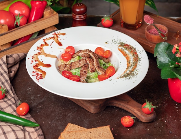 Healthy grilled beef caesar salad with cheese, cherry tomatoes and lettuce