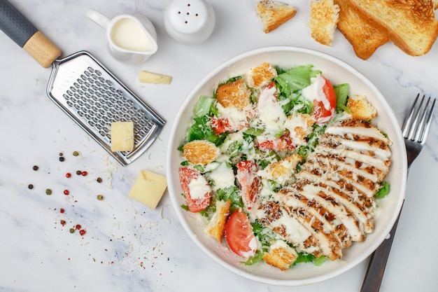 Healthy grilled chicken caesar salad with lettuce, cheese, tomatoes, croutons and gourmet sauce
