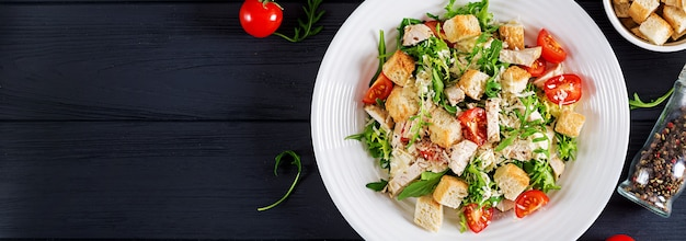 Healthy grilled chicken caesar salad with tomatoes, cheese and croutons. north american cuisine. banner. top view