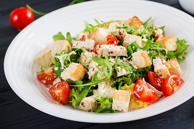Healthy grilled chicken caesar salad with tomatoes, cheese and croutons