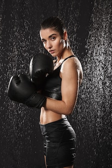 Healthy gymnastic woman kickboxing in gloves and standing in defense position under rain drops, isolated over black background