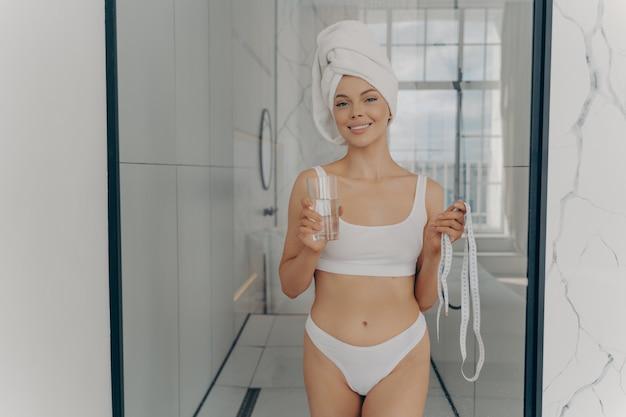 健康的な習慣。シャワーの直後に、水のバランスを純粋なミネラルガラスの水で補充し、テープラインで自分自身を測定する準備ができて、自宅で朝のルーチンを楽しんでいる幸せな魅力的なスリムな女性