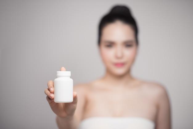 Здоровая счастливая азиатская женщина с бутылкой пилюлек в руке.