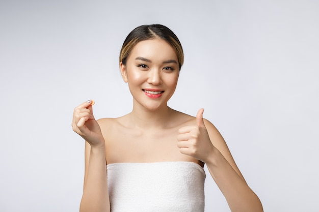 Healthy happy asian woman with pills in hand isolate over white background.