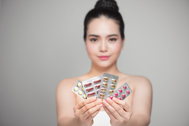 手に丸薬を持つ健康な幸せなアジアの女性。