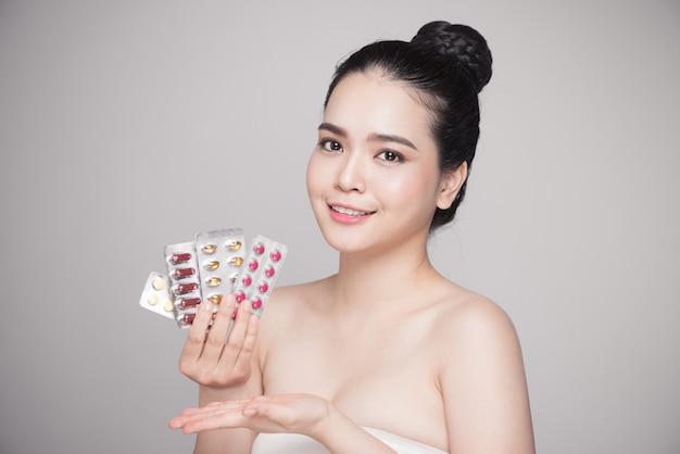 손에 약을 들고 건강한 행복한 아시아 여성.