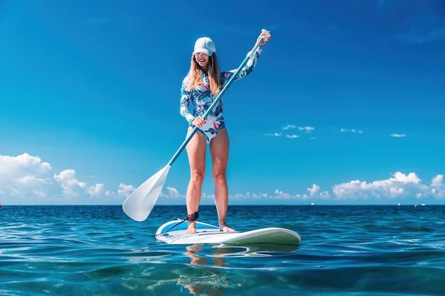 澄んだターコイズブルーの海に浮かぶsupサーフボードでリラックスしたビキニの健康的な幸せなフィットの女性