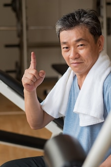 Healthy, happy senior man working out in gym, giving no.1 finger gesture, winning or success concept
