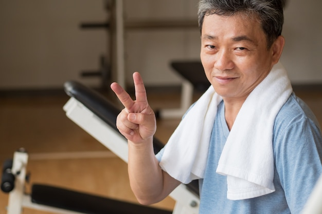 Healthy, happy senior man working out in gym, giving no.2 finger gesture, victory or success concept