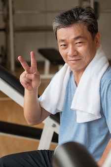 Healthy happy senior man working out in gym giving no finger gesture victory or success concept