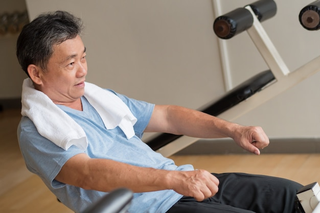 Healthy happy smiling positive senior well being asian man working out ab muscle in gym