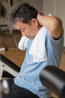 Healthy, happy, smiling, positive senior well being asian man working out ab muscle in gym