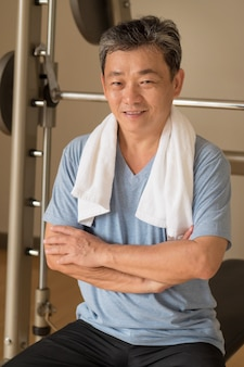 Healthy happy smiling positive senior well being asian man working out in gym