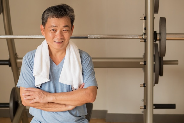 Healthy, happy, smiling, positive senior well being asian man working out in gym