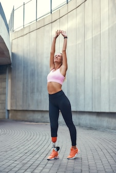 Healthy and happy young smiling woman with leg prosthesis in sports clothing stretching before