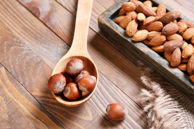 Healthy hazelnut and almond nuts on wooden surface