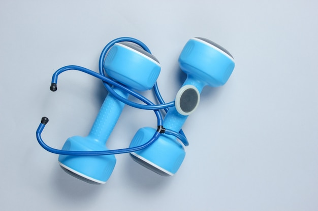 Healthy heart and strong muscles. blue plastic dumbbells and stethoscope on gray.