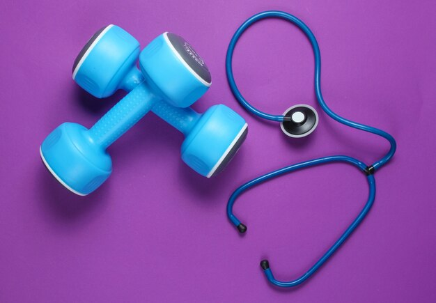 Healthy heart and strong muscles. blue plastic dumbbells and stethoscope on purple.
