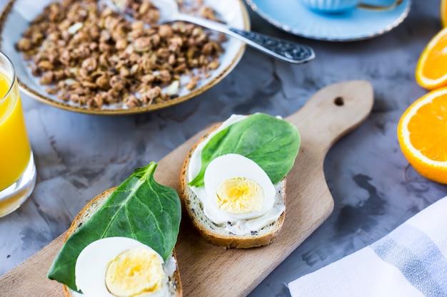 健康的なボリュームのある朝食 - ミューズリー、卵、コーヒー、オレンジ、ジュースのサンドイッチ