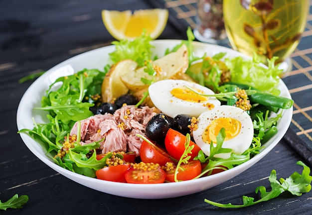 Healthy hearty salad of tuna, green beans, tomatoes, eggs, potatoes, black olives close-up in a bowl on the table.