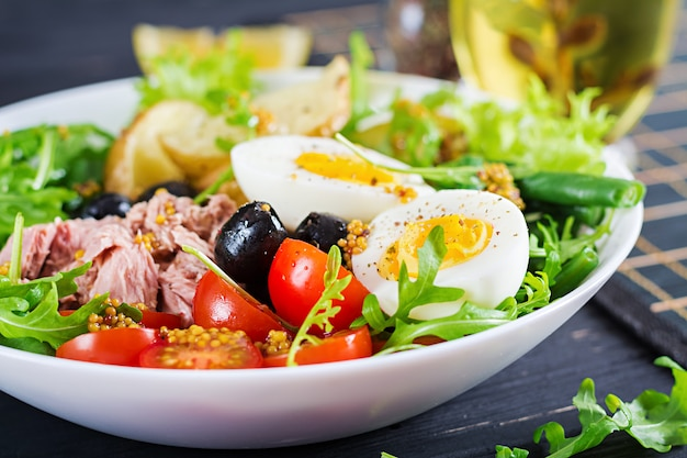 Healthy hearty salad of tuna, green beans, tomatoes, eggs, potatoes, black olives close-up in a bowl on the table